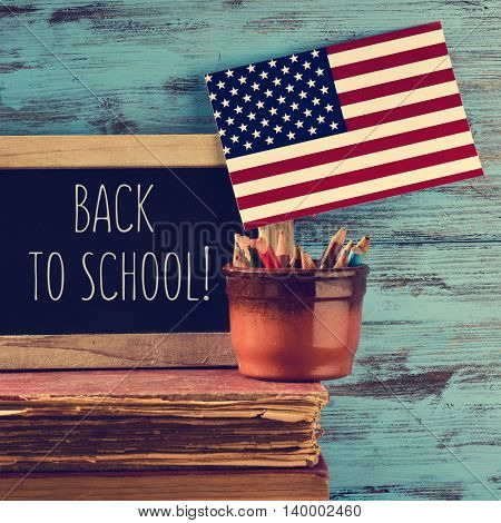 a chalkboard with the text back to school and a flag of the United States in a pot with pencil crayons on a pile of old books, against a rustic blue wooden background