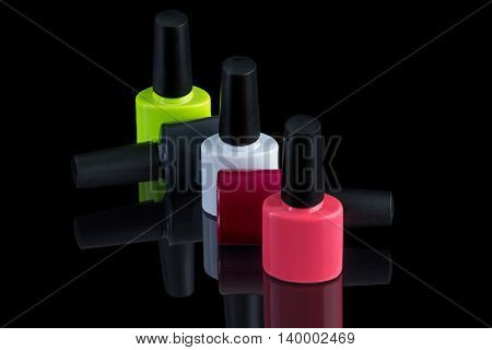 multi-colored bottles of nail polish on a black background with the reflected shadow