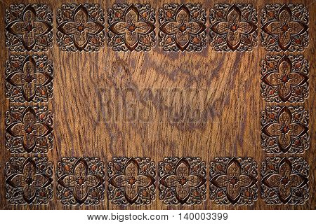 embossed floral frame on a wooden surface