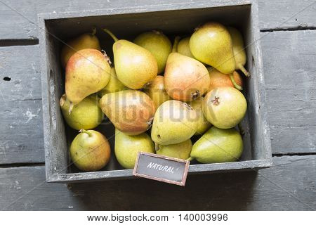 Healthy Organic Pears on the table in the box and the text natural
