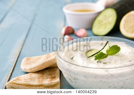 Tzatziki sauce in bowl and ingredients on a blue wooden table