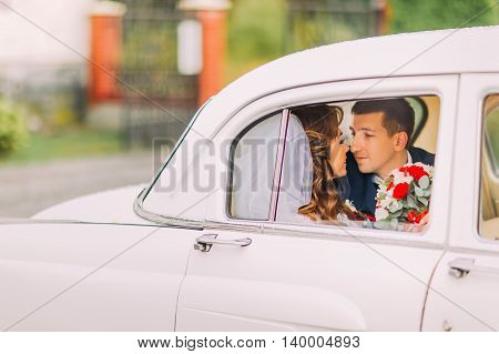 Happy newlywed couple kissing on a backseat of vintage car.