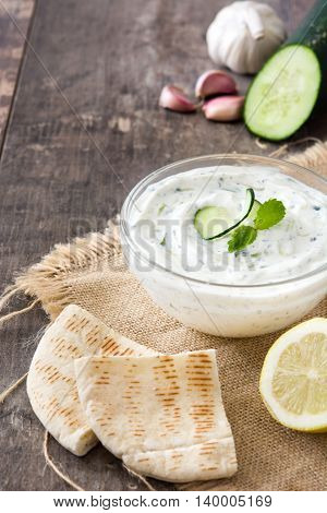 Tzatziki, pita bread, cucumber, garlic and olive oil on a wooden table