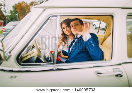 Happy newlywed couple sitting in vintage car. Groom is waving his hand to the attendants.