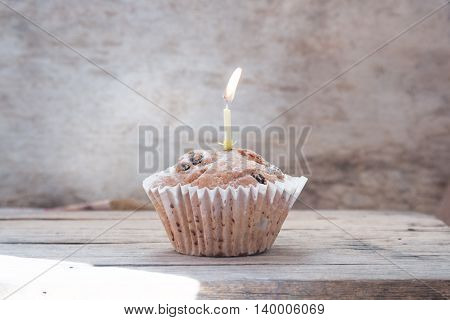 Birthday cake with one candle on a wooden background