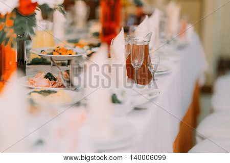 Glasses, food and drinks on table in restaurant.