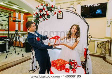 Happy bridal couple with presents at wedding party.