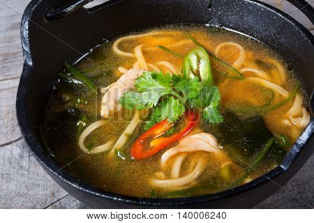Asian noodles soup with seaweed served in a metal bowl