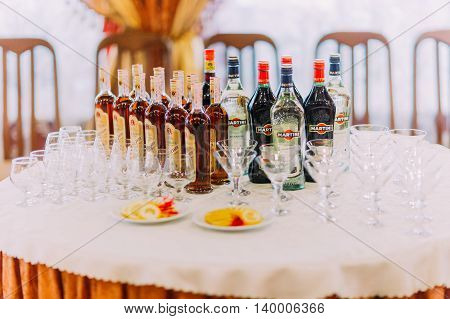 Restaurant table setting with glasses and bottles full of delicious wines. Close-up view.