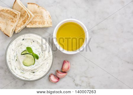Tzatziki, pita bread, cucumber, garlic and olive oil on marble background