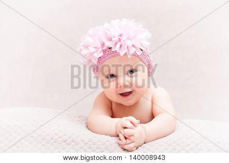 portrait of caucasian newborn with pink flower woolen hat