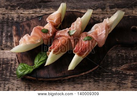 Fresh Melon With Prosciutto And Basil On Vintage Wooden Background