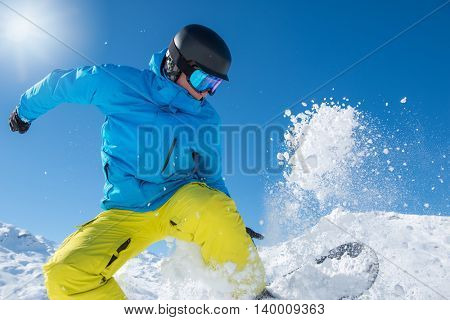 Portrait of an active man on snowboard jumping in snow