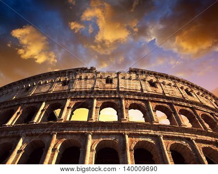 Flavian Amphitheatre or Colosseum in Rome with sunset sky in the background, Italy
