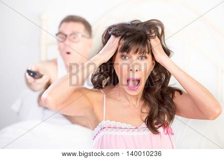 Frustrated Woman And  Man In Bed With Watching Tv
