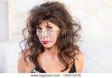 Upset mature woman crying in her bedroom with smeared makeup