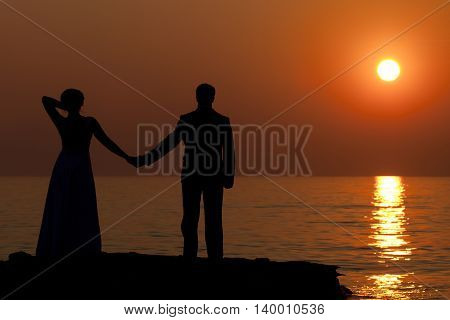 a couple of admiring the sunset on the sea