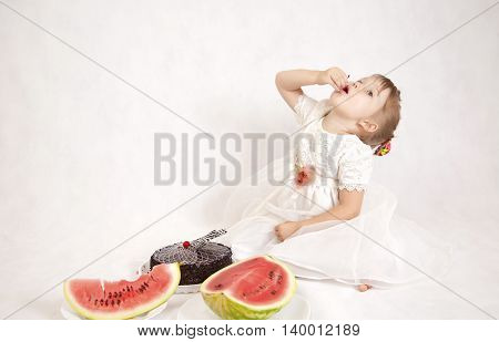Little happy girl eats a delicious cake and juicy watermelon