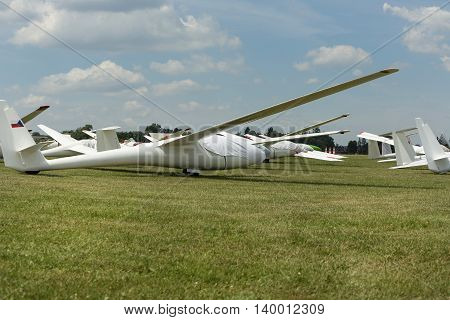 gliders at green airfield with blue sky in sunny day