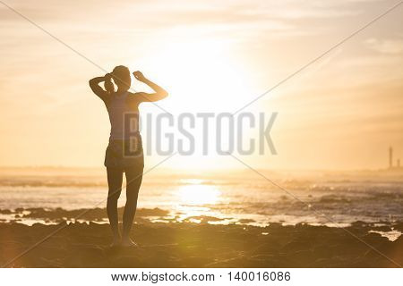 Silhouette of sporty woman clamping her hair in a ponytail while watching sunset at the beach.