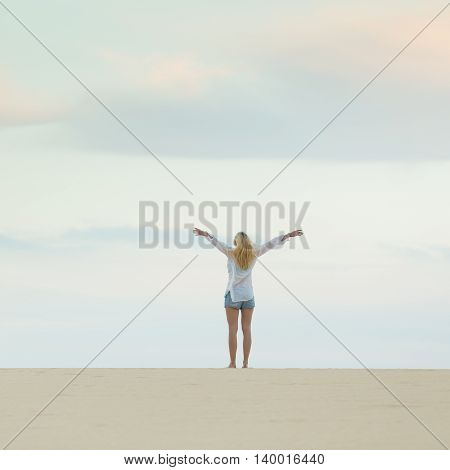 Relaxed woman enjoying freedom feeling happy at beach at dusk. Serene relaxing woman in pure happiness and elated enjoyment with arms raised outstretched up.