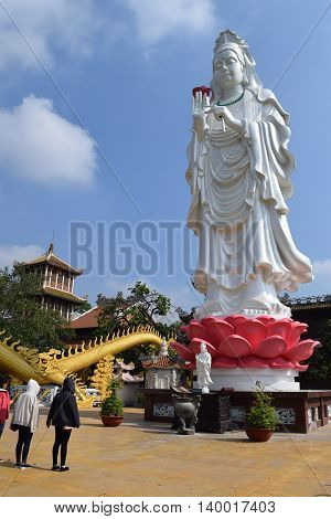 Binh Duong Vietnam June 16 2016: people praying at the big statue of Bodhisattva at Buddhist Chau Thoi temple