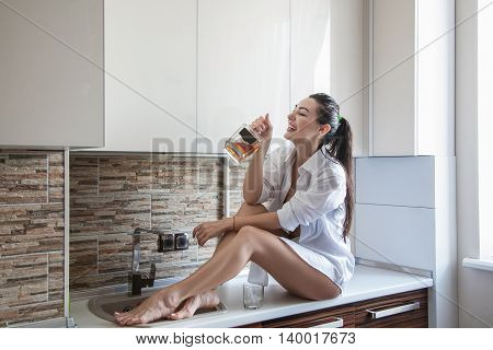 Woman With Bottle At Kitchen