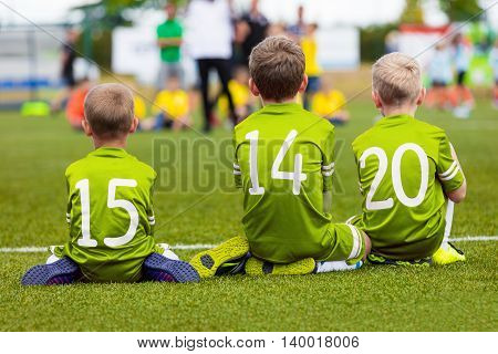 Young players of soccer team. Kids as reserve players on football bench watching soccer game and supporting green team. Soccer school tournament for youth soccer teams.