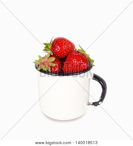 Fresh ripe red strawberries in enamel mug over white background copy space