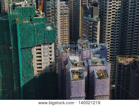 Construction site with scaffolds made of bamboo. Rooftop gardens. Scene in the centre of Hong Kong. Dense architecture.