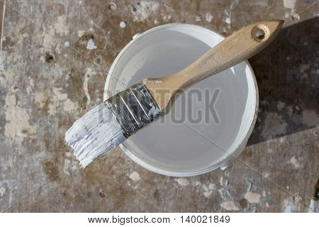 Brush in white paint in a bucket viewed from above