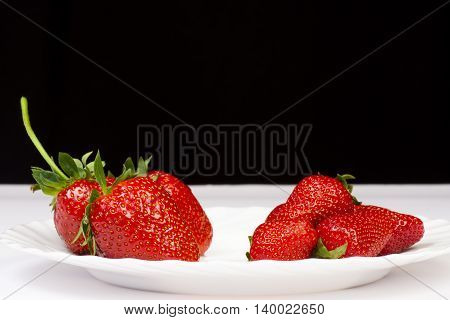 Big and small strawberries are on white plate on black background.