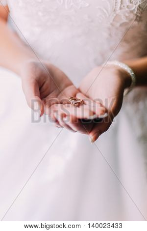 Bride holding wedding ring on her hands.