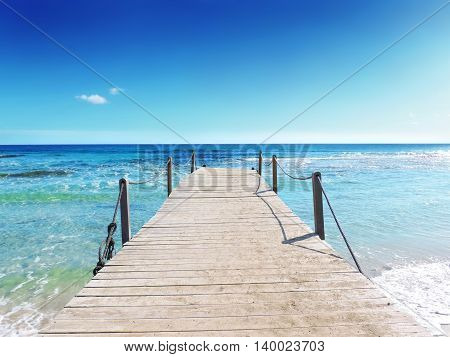 Boardwalk into the sea. Gangplank and turquoise colored water. Tropical sea scene.