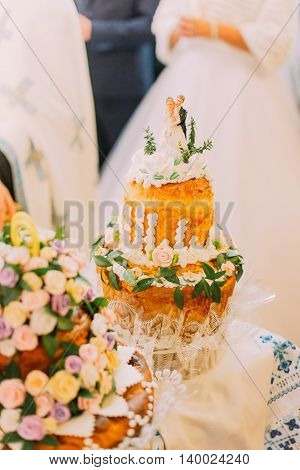 Beautifully decorated traditional wedding bread with blurred couple on background.