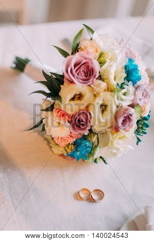 Close-up of beautiful bridal bouquet with pair golden wedding rings.