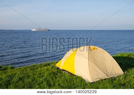 The River Kama. Tourist tent on the shore of the Kuibyshev reservoir. On the horizon floats a tourist motor ship.