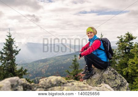 Woman hiking in autumn mountains and woods. Sitting on rock and relaxing recreation and healthy lifestyle outdoors in fall nature. Beauty blond looking at camera on sunset inspirational landscape.