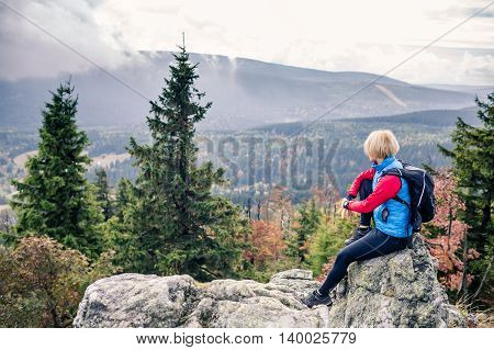 Woman hiker celebrate on mountain top in autumn landscape and woods. Sitting on rock and relaxing recreation and healthy lifestyle. Beauty blond looking at sunset inspirational landscape view.
