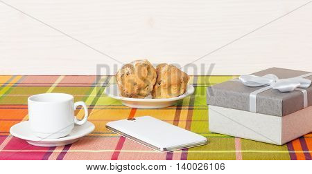 White coffee Cup muffins smartphone on the table