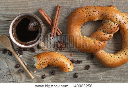 Cup of hot coffee with soft pretzels for breakfast on wooden table top view