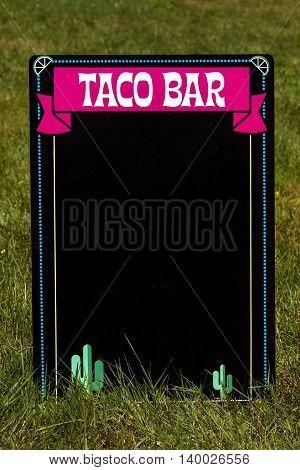 A taco bar chalkboard sitting in the grass