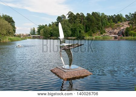 KOTKA, FINLAND - JUNE 26, 2016: Metal sculpture composition in the pond of Sapokka Water Garden. On the background are waterfall and bridge.