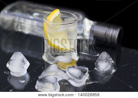 A glass of vodka with ice and lemon on a black background close-up
