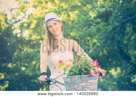 Elegant female on vintage hipster bike with basket full of flowers in a park. Active people, vacation, and lifestyle concepts. Retro styled image.