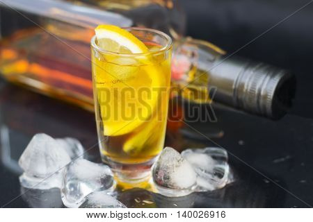 A glass of cognac with ice and lemon on a black background close-up