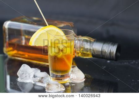 A glass of cognac with ice on black background close-up