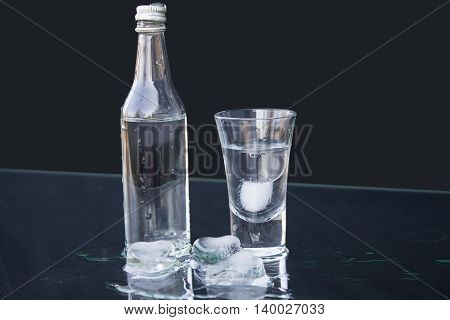 Vodka. Small bottle of vodka with a shot glass. black background closeup