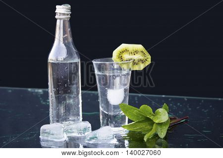Vodka. Small bottle of vodka with a glass ice and kiwi on the table. black background closeup