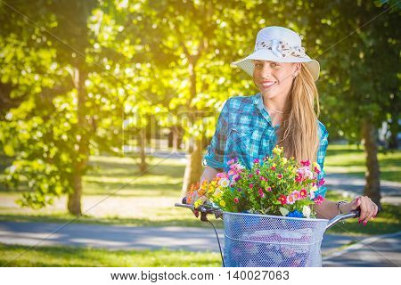 Elegant female on retro hipster bike with basket full of flowers in a park. Active people, vacation, and lifestyle concepts. Space for copy.